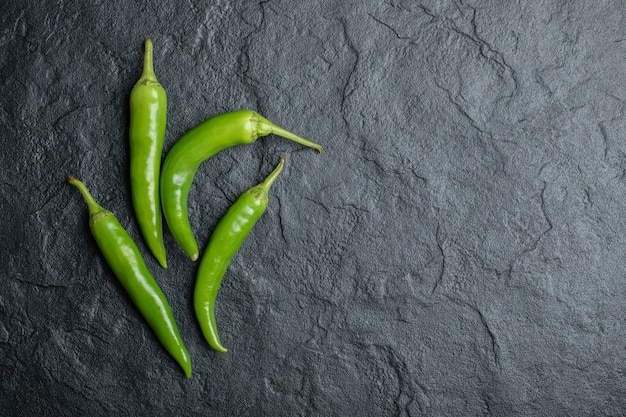 Top view of green hot peppers on black background