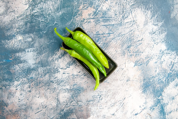 Top view green hot peppers on black plate on blue-white background