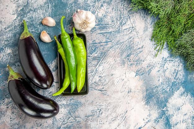上面図青白の背景に黒のプレートにんにく茄子の緑の唐辛子