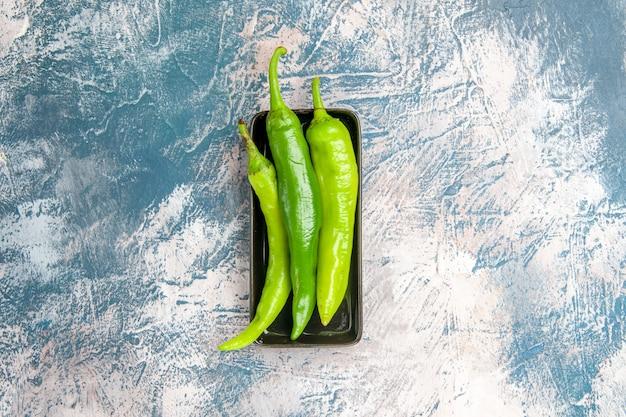 青白の背景の上の黒いプレート上の上面図緑唐辛子