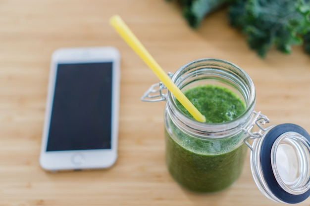 Top view of green juice with straw