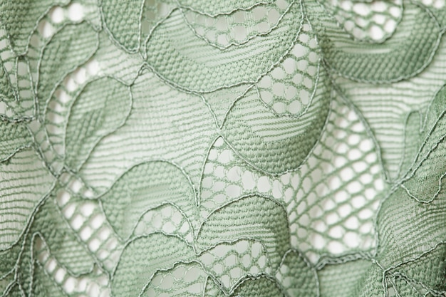 Top view over green lace textil texture with ornament. macro shot
