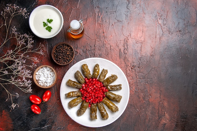 Top view of green leaf dolma with pomegranates on dark surface