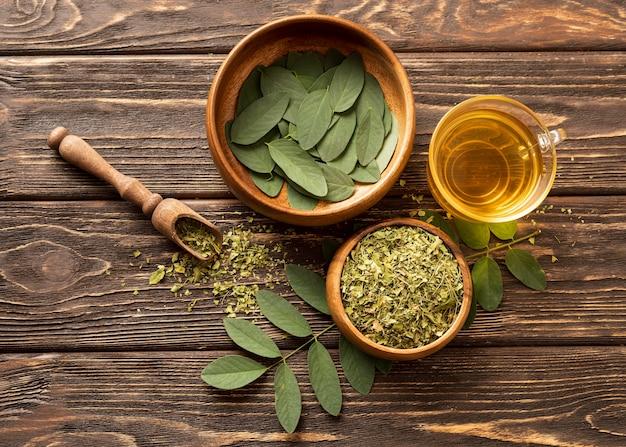 Вид сверху зеленые листья и чашка чая