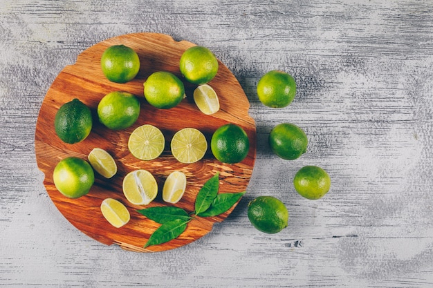 Top view green lemons in wooden platform with slices and leaves on gray wooden background. horizontal