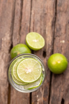 Top view green lime sliced in the soda water and glass place on the wooden table