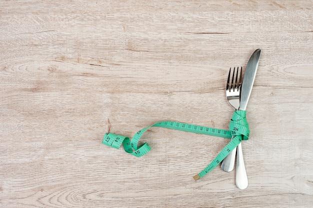 上面図緑の測定テープは、木製のテーブルの背景にフォークとナイフの周りに巻かれています。ダイエット、減量、肥満、食品管理の概念