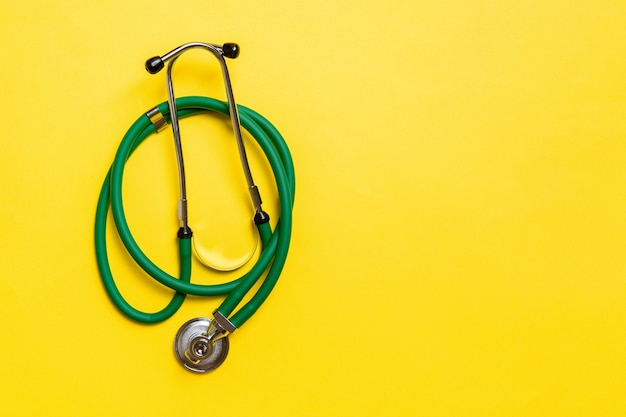 Top view of green medical stethoscope on colorful background with copy space
