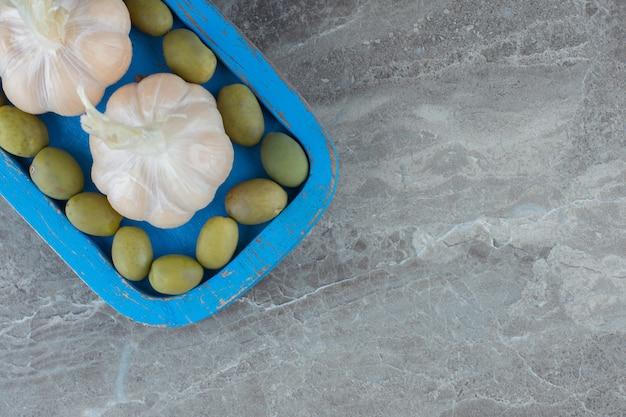 Vista dall'alto di oliva verde con aglio su piatto di legno blu.