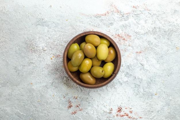 Olive verdi di vista dall'alto all'interno del piccolo piatto su uno spazio bianco