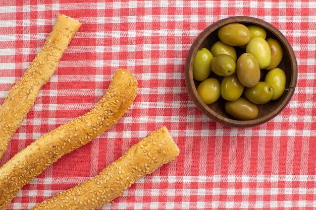 Vista dall'alto di olive verdi con focacce di pane sulla verdura farina di cibo del tessuto