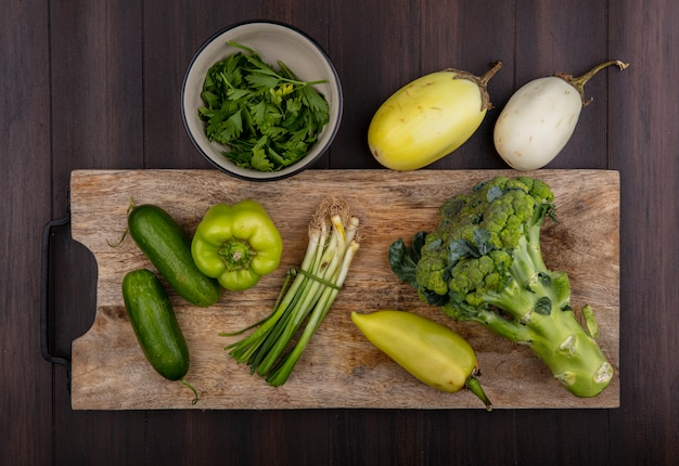 Vista dall'alto di cipolle verdi con cetrioli e peperoni verdi broccoli su un tagliere con prezzemolo in una ciotola su uno sfondo di legno