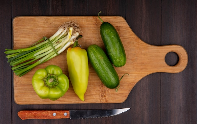 Top view green onions with cucumbers and green peppers on a cutting board with a knife on a wooden background