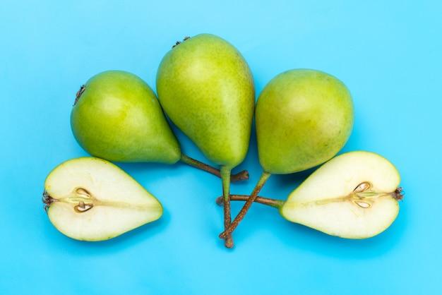 Una vista dall'alto pere verdi affettate e intere dolci e pastose su blu, colore maturo succo di frutta