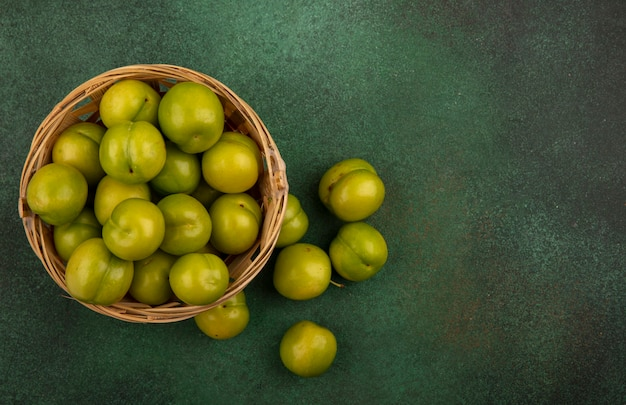 Top view of green plums in basket and on green background with copy space