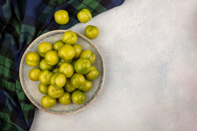 Top view of green plums in plate on plaid cloth and on white background with copy space