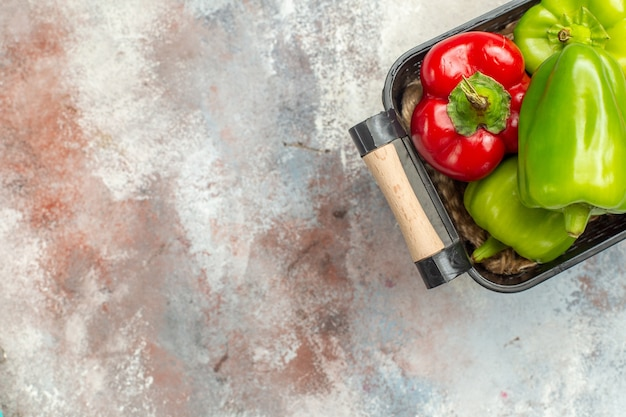 Top view green and red peppers in bowl on nude surface with free space