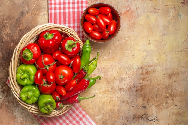Top view green and red peppers hot peppers tomatoes in wicker basket cherry tomatoes in bowl kitchen towel on amber background