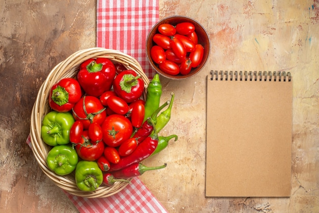 Top view green and red peppers hot peppers tomatoes in wicker basket cherry tomatoes in bowl kitchen towel a notebook on amber background