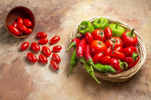 Vista dall'alto peperoni verdi e rossi peperoni piccanti pomodori in cesto di vimini pomodorini sparsi dalla ciotola su sfondo ambrato