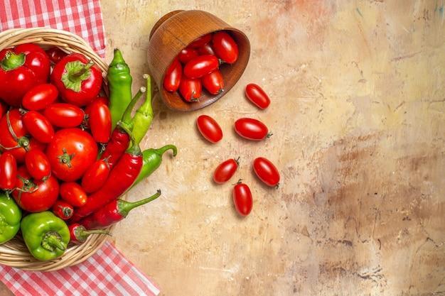 Vista dall'alto peperoni verdi e rossi peperoni piccanti pomodori in cesto di vimini pomodorini sparsi dalla ciotola asciugamano da cucina su sfondo ambra
