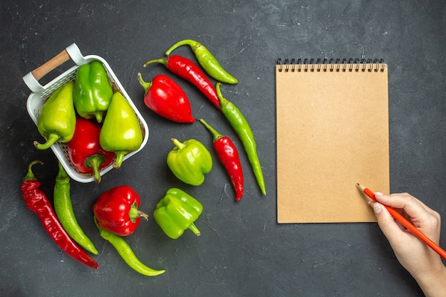 Top view green and red peppers in plastic basket hot peppers a notebook pencil in woman hand on dark surface