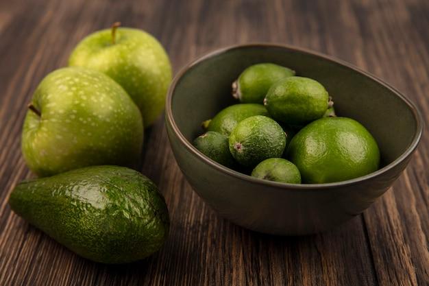 Vista dall'alto di feijoas maturi verdi con limette su una ciotola con mele verdi e avocado isolato su una parete in legno