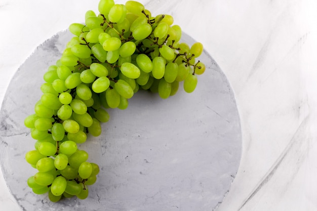 Вид сверху зеленые спелые ягоды винограда на фоне мрамора