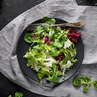 Вид сверху зеленый салат на темной тарелке