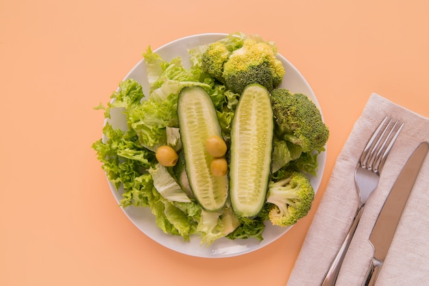 Top view green salad with cutlery