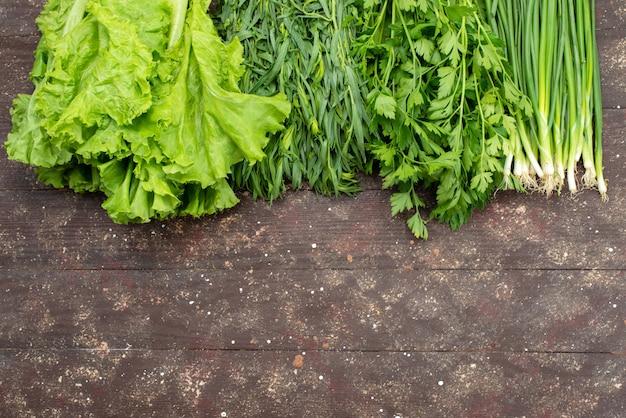 Вид сверху зеленый салат с зеленью на коричневом, овощном зеленом листе