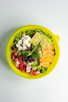 Top view of green salad with lettuce cherry tomato avocado orange corn and mozzarella