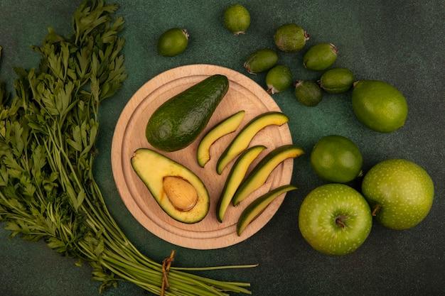 Vista dall'alto di avocado dalla pelle verde con fette su una tavola da cucina in legno con coltello con lime, mele verdi, feijoas e prezzemolo isolato su una superficie verde
