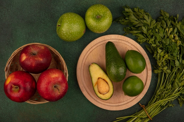 Top view of green skinned avocados on a wooden kitchen board with limes with red apples on a bucket with green apples and parsley isolated on a green background