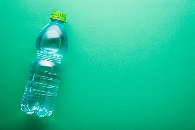 Вид сверху зеленая маленькая пластиковая бутылка чистой чистой питьевой воды с копией пространства на мяте нео
