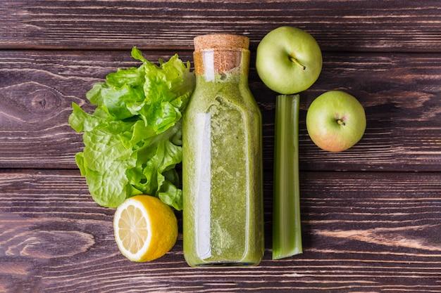 Bottiglia di frullato verde vista dall'alto con ingredienti