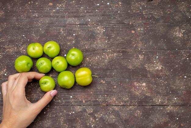 トップビューグリーンサワーチェリープラム並ぶまろやかで新鮮な木製の素朴な背景の果物色のまろやか