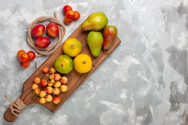 Вид сверху зеленые мандарины с черешнями, сливами и грушами на светлом белом столе.