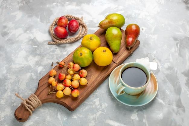 Вид сверху зеленые мандарины с черешни, сливы, чай и груши на светлом белом столе.