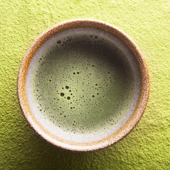 Top view of green tea matcha in a bowl on a powdered surface