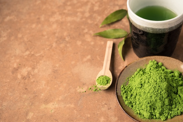 Top view of green tea powder with tea cup on the table. free space for text