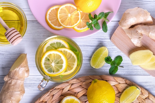 Top view of green tea with lemon ginger and honey in a glass cup with oranges around on wooden table