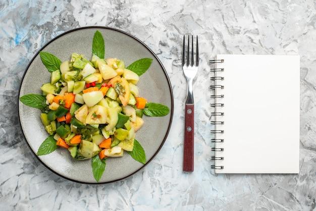 회색 배경에 타원형 접시에 있는 상단 보기 녹색 토마토 샐러드 포크 메모장