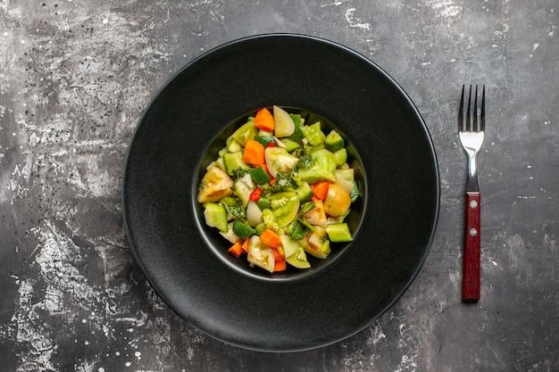 Вид сверху салат из зеленых помидоров на овальной тарелке вилкой на темном фоне