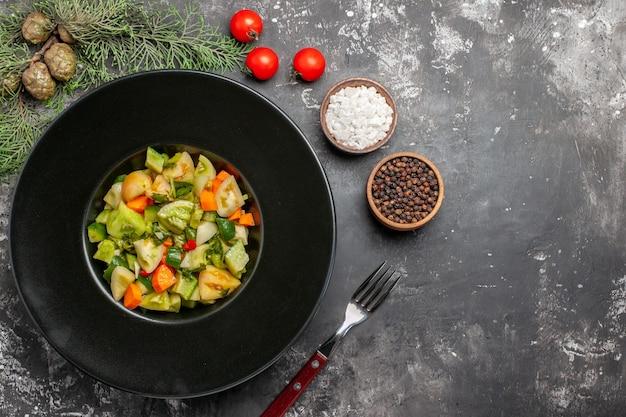 楕円形のプレートにグリーントマトのサラダ、暗い背景にフォークソルトと黒胡椒を上から見た図