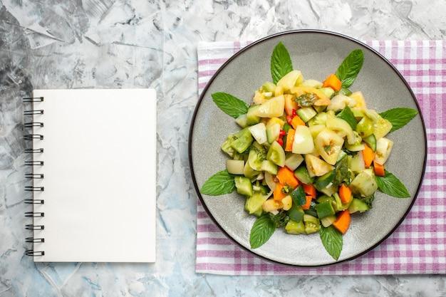 어두운 배경에 타원형 접시 메모장에 상위 뷰 녹색 토마토 샐러드