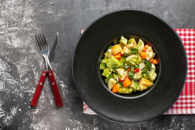 Вид сверху салат из зеленых помидоров на овальной тарелке, скрещенные нож и вилка на темном фоне