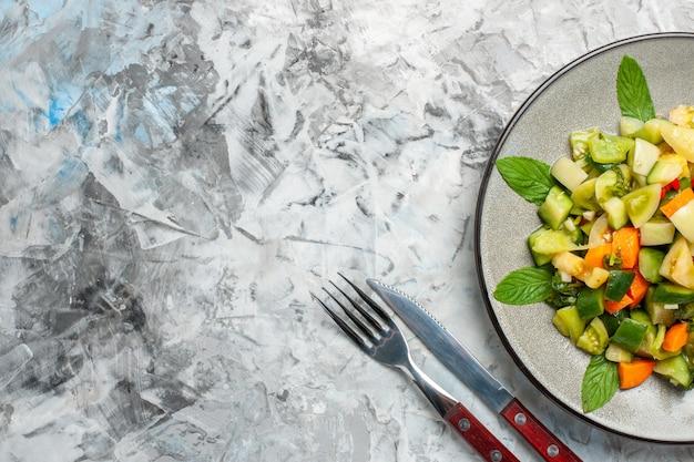 Вид сверху салат из зеленых помидоров на овальной тарелке, вилке и ноже на сером фоне