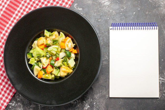 暗い背景の楕円形のプレートノートブックの上面図グリーントマトサラダ