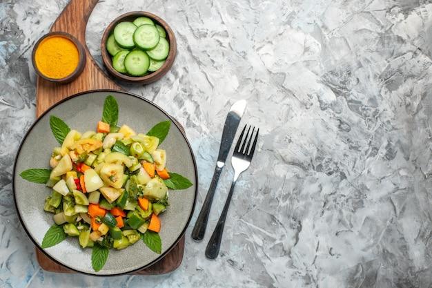 まな板の上の楕円形のプレート上の上面図グリーントマトサラダフォーク暗い背景の上のナイフ